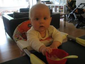 Baby starting solids sitting in baby chair