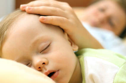Cosleeping mom with hand on baby s head