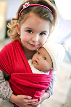 Toddler girl with doll baby carrier