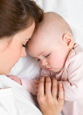 Baby girl settling to sleep next to mother