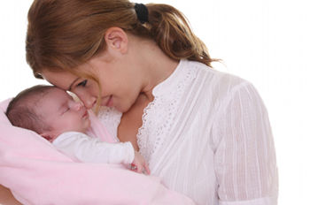 Newborn in pink blanket, with mother