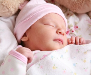 Newborn sleeping with pink hat