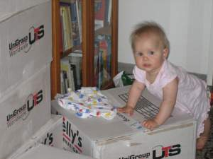 Ten months old baby unpacking removal boxes