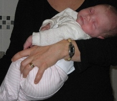 Two weeks old baby in mothers arms