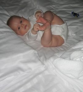 Five and a half months old baby playing on hotel bed
