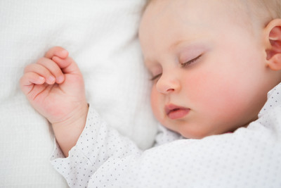 Gorgeous baby asleep with hand on the side