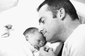 Newborn sleeping near daddy