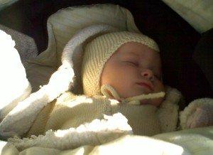 Six months old baby sleeping in pram