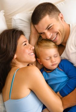 Baby sleeping in bed with happy mother and father